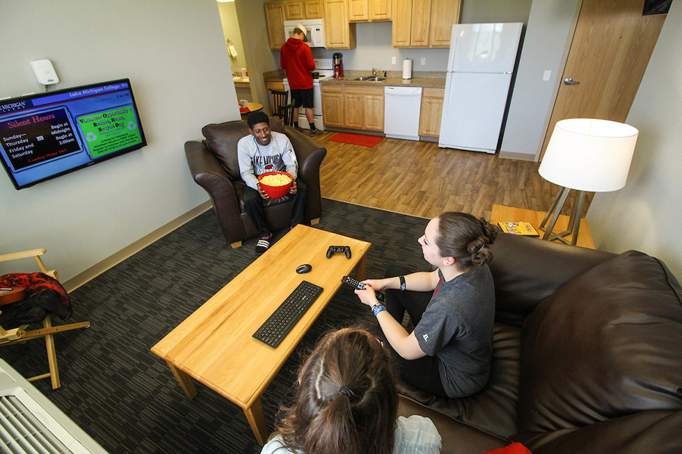 Students in shared living spaces in a dorm suite.