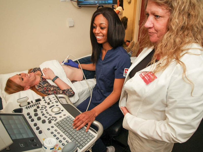 Sonography student with instructor in classroom