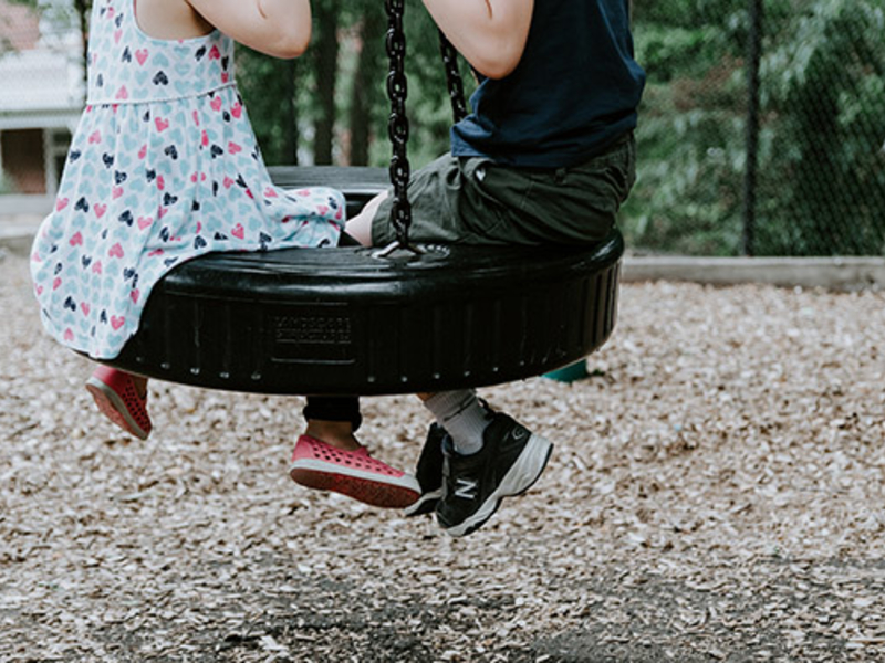 Children playing on a tire swing