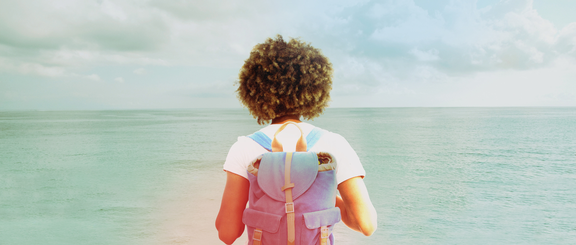 Woman with backpack looking toward the horizon