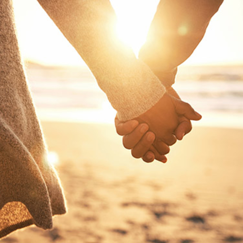 Couple holding hands at the beach at sunset