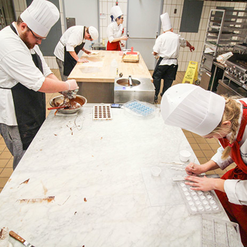 Students working with chocolate in the teaching kitchen.
